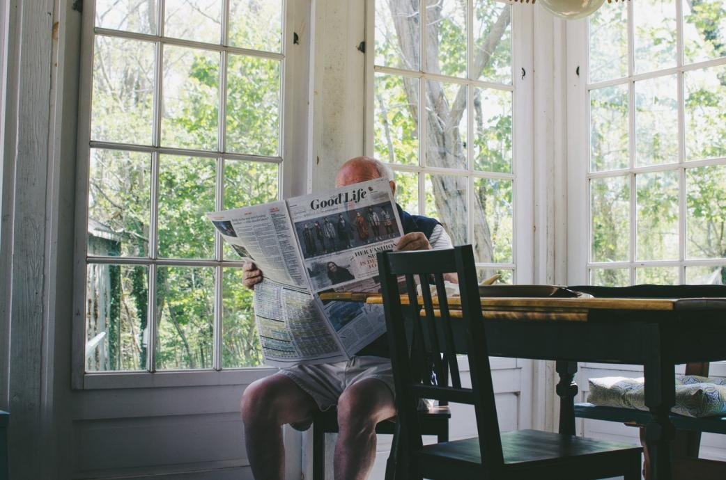 Photo courtesy of Unsplash of man reading newspaper