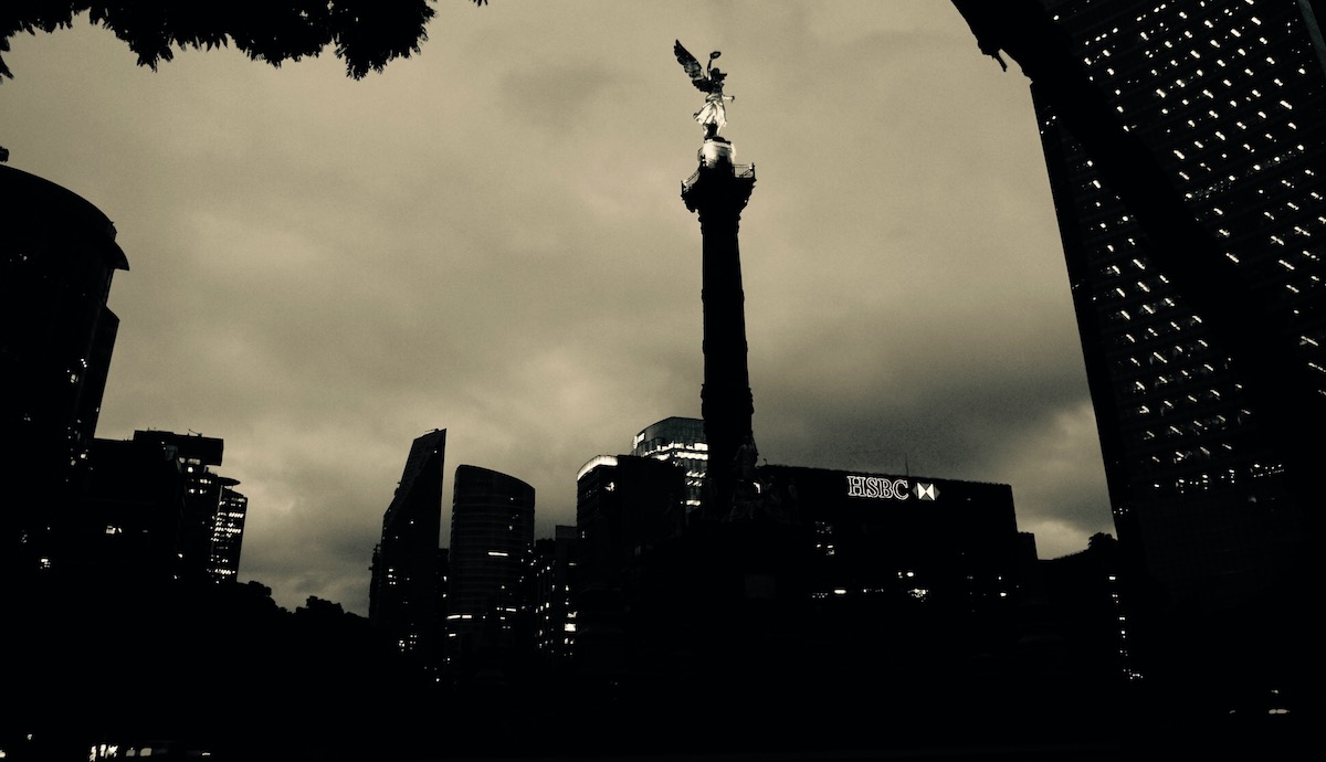 Angel, a photo by Nicolas Poynter. It shows a city and building with an angel sculpture on the tip.