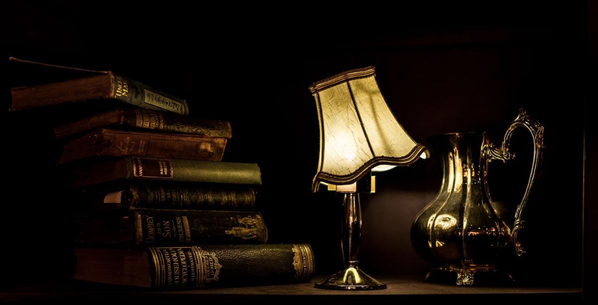 lamp and books on a table, lampshade is crooked