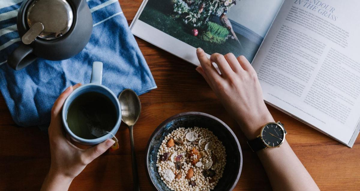 Image of a person eating breakfast and reading