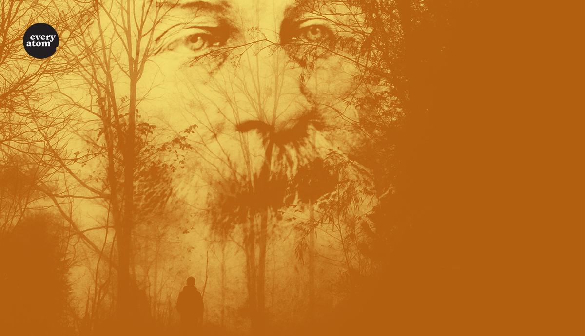 Whitman's face through a treeline