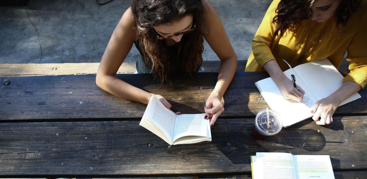 Image of women reading and writing at a table courtesy of Unsplash