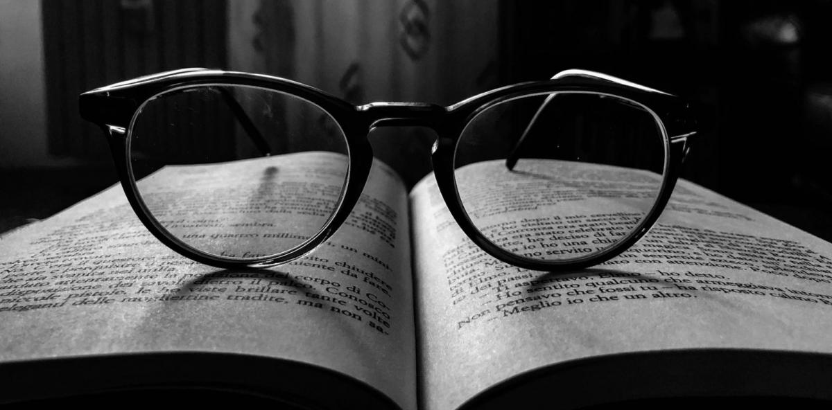 black and white image of glasses resting on an open book