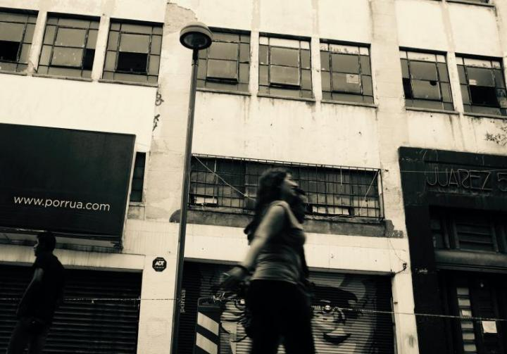 Juarez, a photo by Nicolas Poynter. It shows people passing by in front of a building.