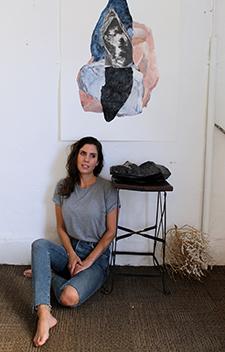 Elizabeth Sims sitting underneath her artwork