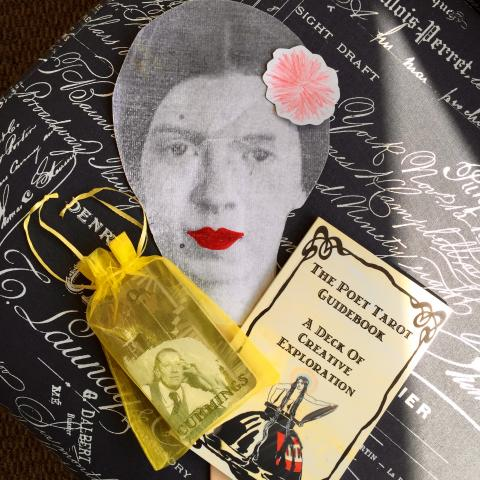 Cutout of a Woman's Face Next to The Poet Tarot Guidebook and Yellow Bag