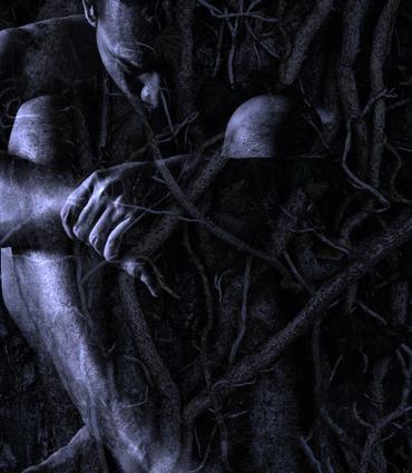 Huddled figure among roots