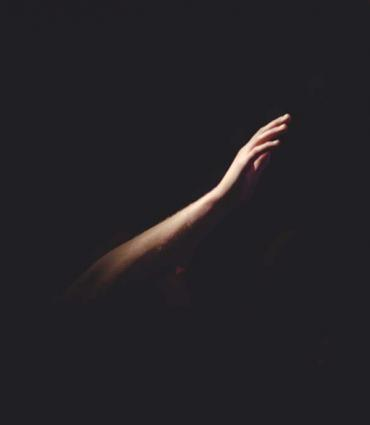A hand reaching out in darkness